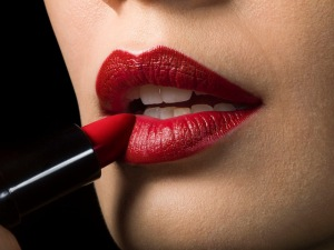 Female applying red lipstick, close up